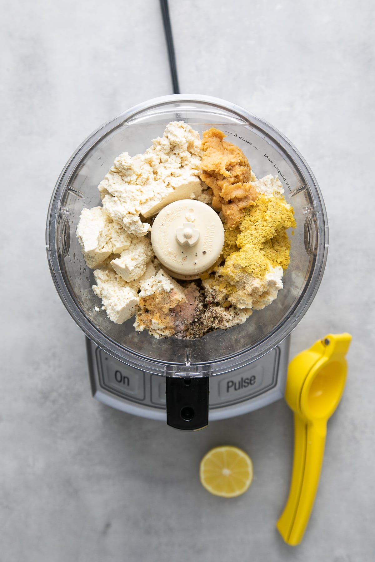 top down view of ingredients to make tofu ricotta added to the bowl of a food processor.