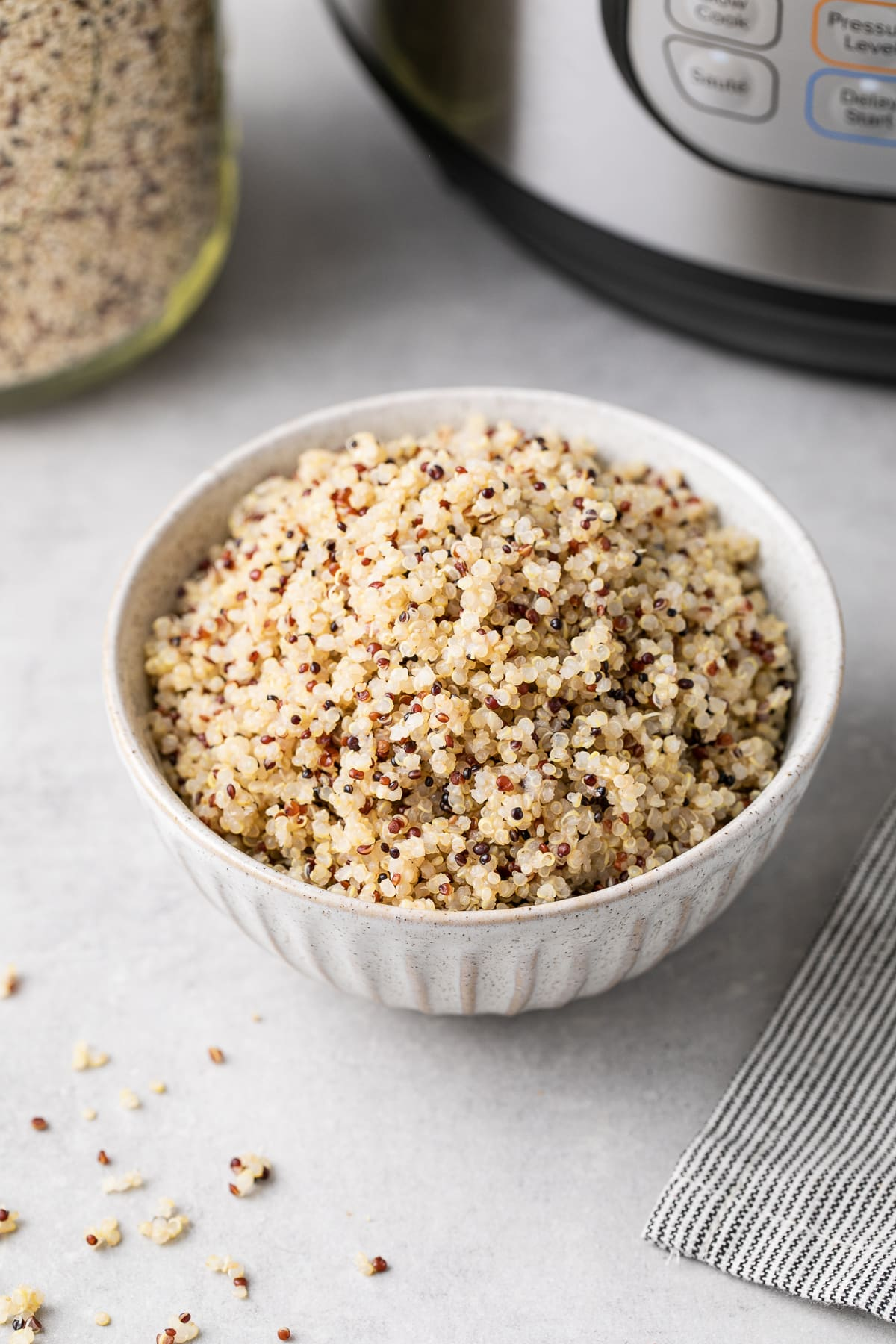 side angle view of a bowl filled with quinoa made in an instant pot with items surrounding.