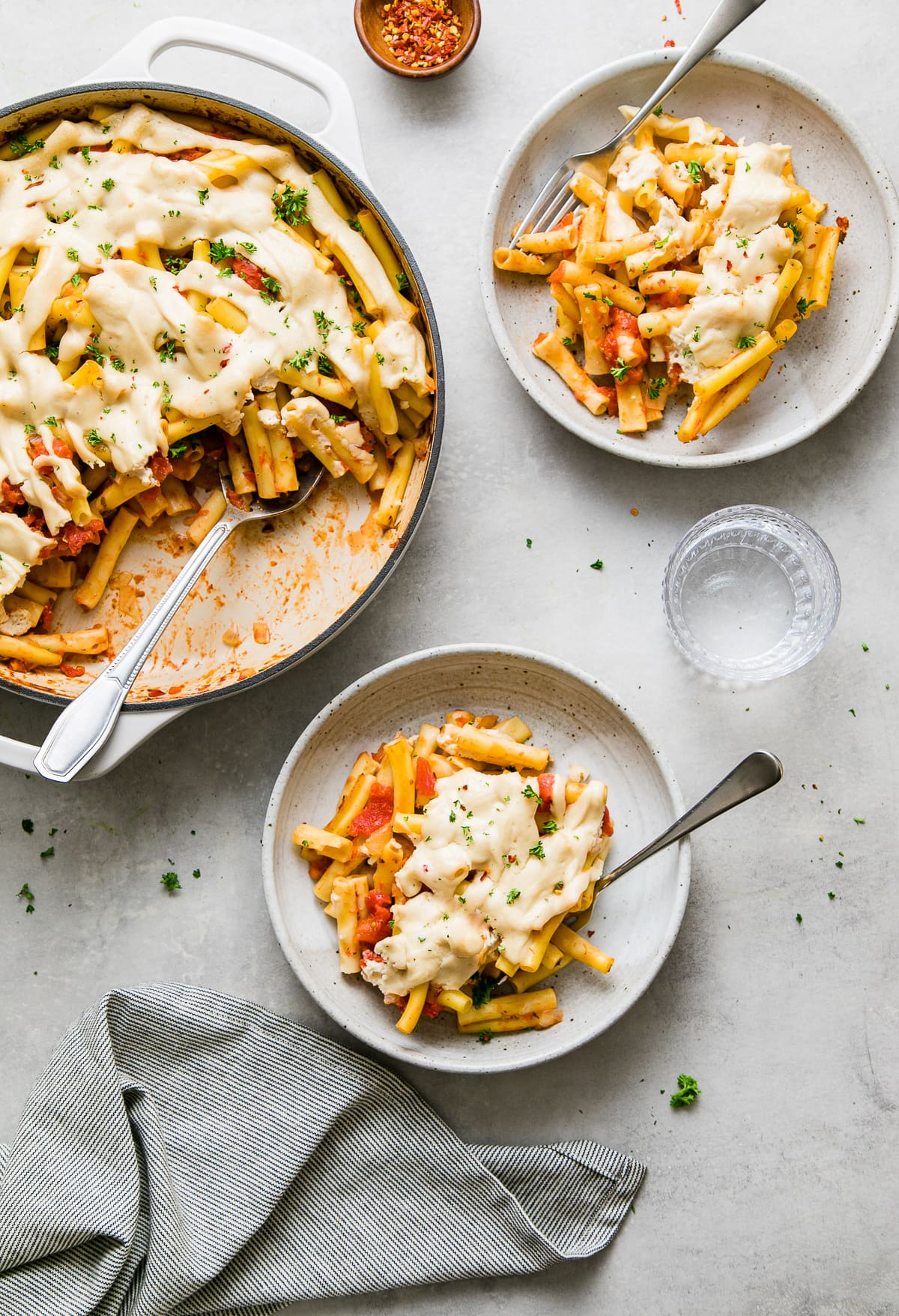 top down view of freshly made vegan baked ziti with items surrounding.