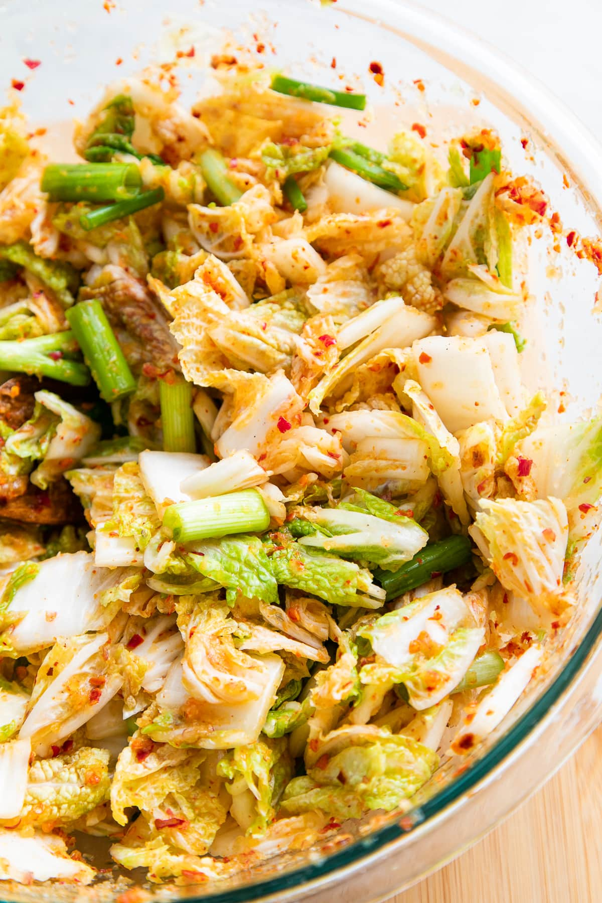 side angle view of freshly mixed cabbage and kimchi seasoning.