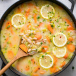 top down view of easy white bean soup in a pot with wooden spoon.