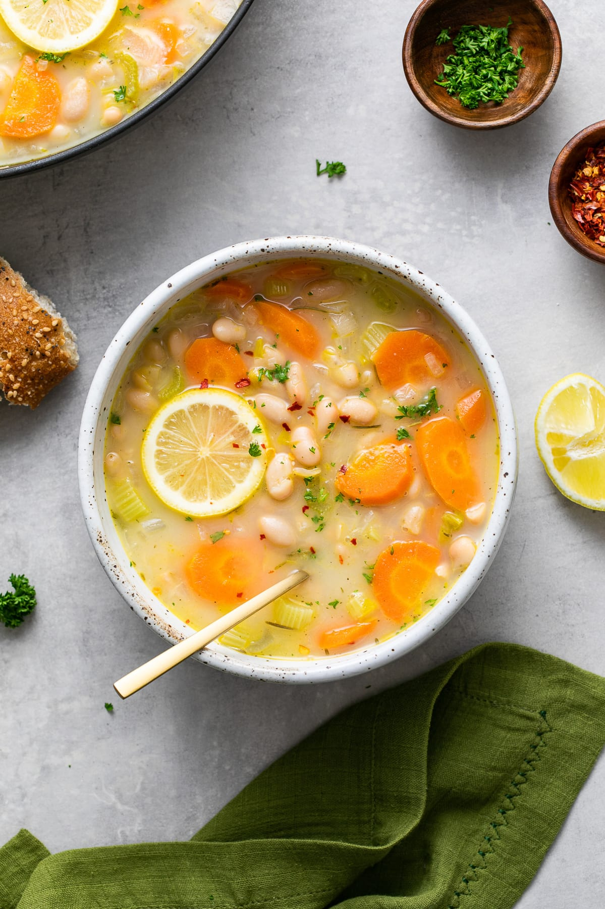 top down view of bowl with serving of lemon white bean soup with spoon and items surrounding.