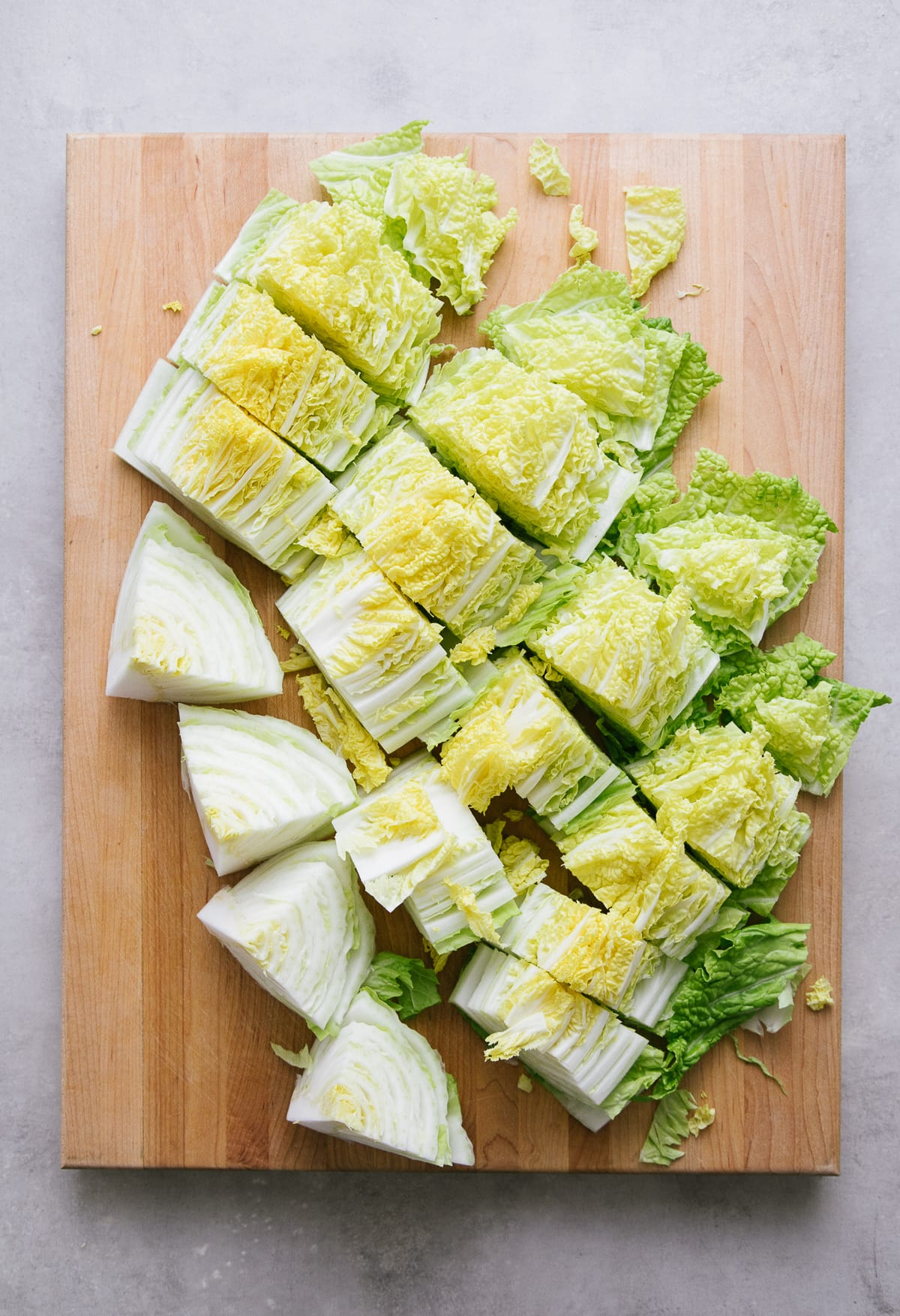 top down view of sliced napa cabbage on a wooden cutting board.