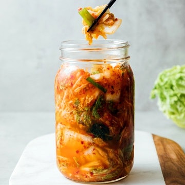head on view of vegan kimchi in a mason jar with chopsticks.