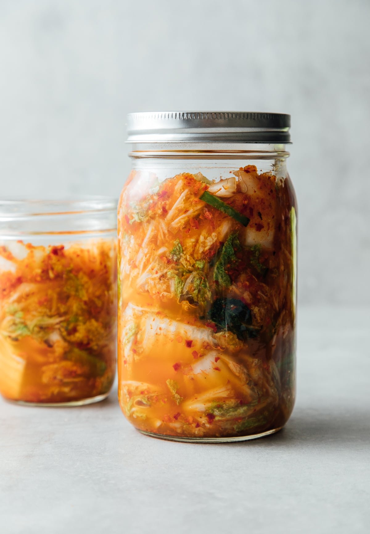 head on view of freshly mixed kimchi added to mason jar before fermenting.