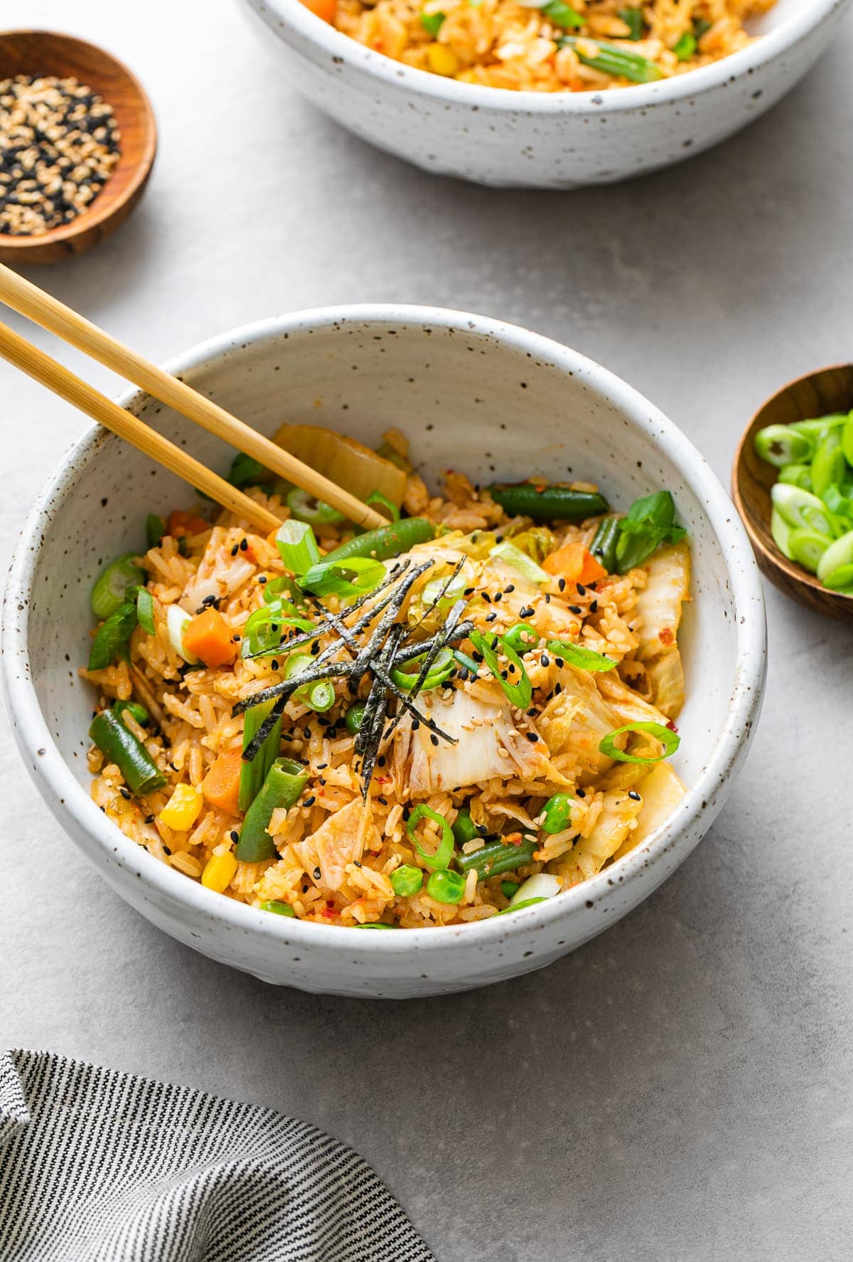 side angle view of bowl with serving of kimchi fried rice with chopsticks.