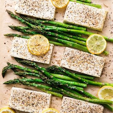 top down view of freshly baked lemon pepper tofu with asparagus on sheet pan.