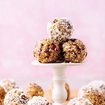 head on view of group of vegan cranberry energy bites on a cupcake stand with items surrounding.