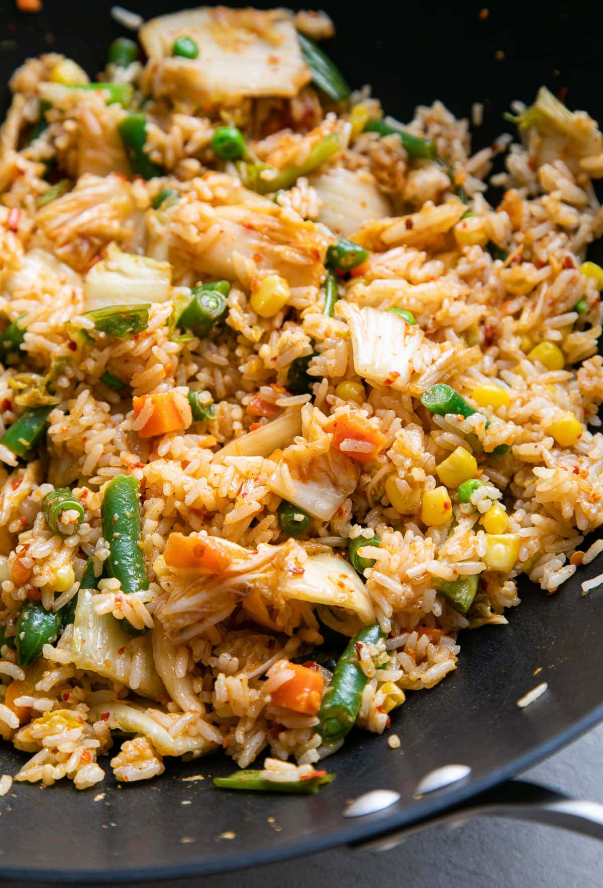 side angle, up close view of vegan kimchi fried rice in a wok.