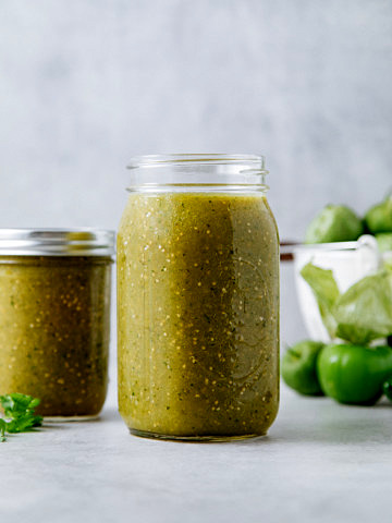 head on view of glass jar filled with homemade tomatillo salsa verde and items in background.