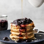 head on view of stacked pancakes with blueberry compote and being drizzled with syrup.