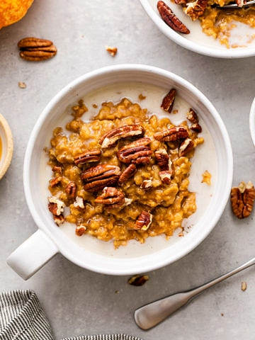 top down view of healthy pumpkin oatmeal in a whole bowl with handle and items surrounding.